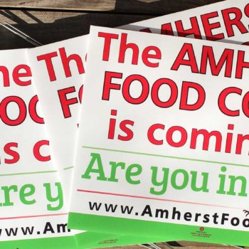Amherst Food Co-op signs laying on a wood deck - Are you In?