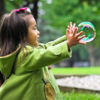 Young Asian Child Playing With Bubbles