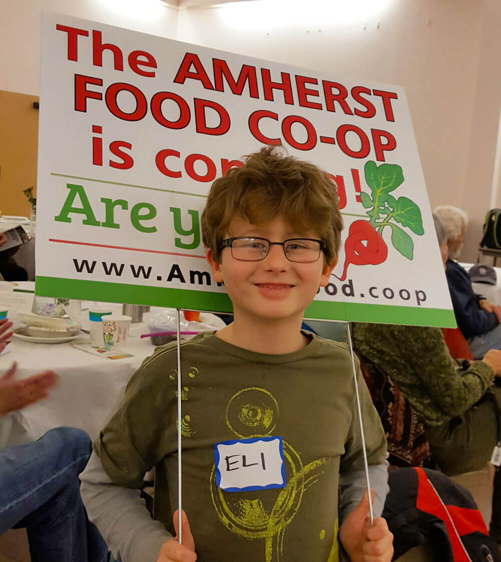young child with Amherst Food Co-op Lawn Sign - Are you in?